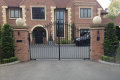 A personalised black, metal gate with two pillars