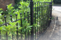 A bespoke metal railing covered in shrubbery