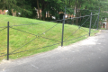 A metal gated railing with a green lawn background