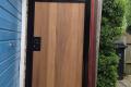 A wooden side gate, adjacent to a garage